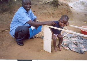A CBR Trainer rehabilitating a Cerebral Palsy child on a parellel bar (Education)